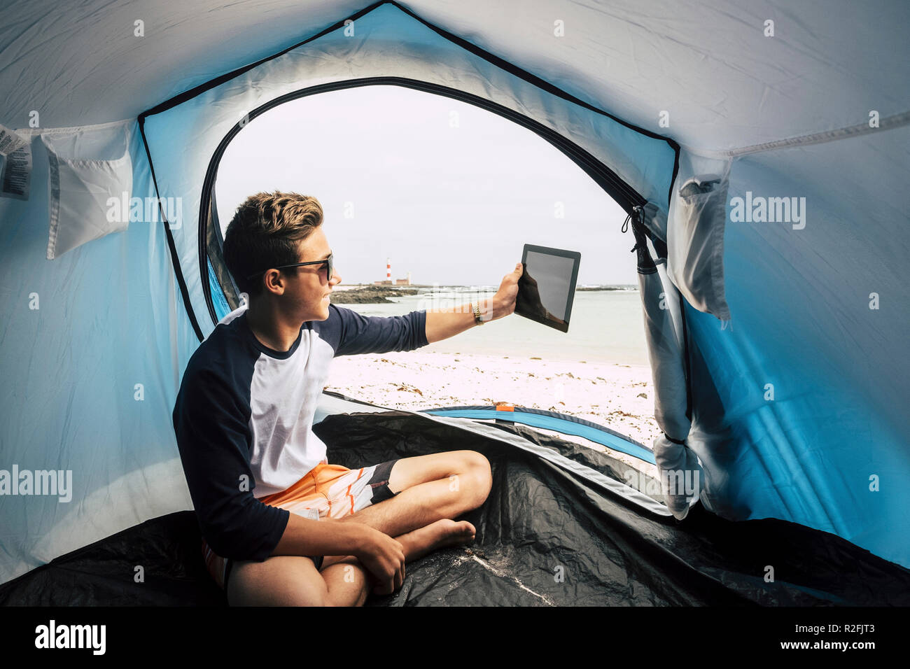 Travel and use technology to communicate for young handsome teenager sitting in side a tent camped on the beach and using a teblaet internet cnnected to send messages and video conference with parents and friends away. alternative vacation concept - Stock Image