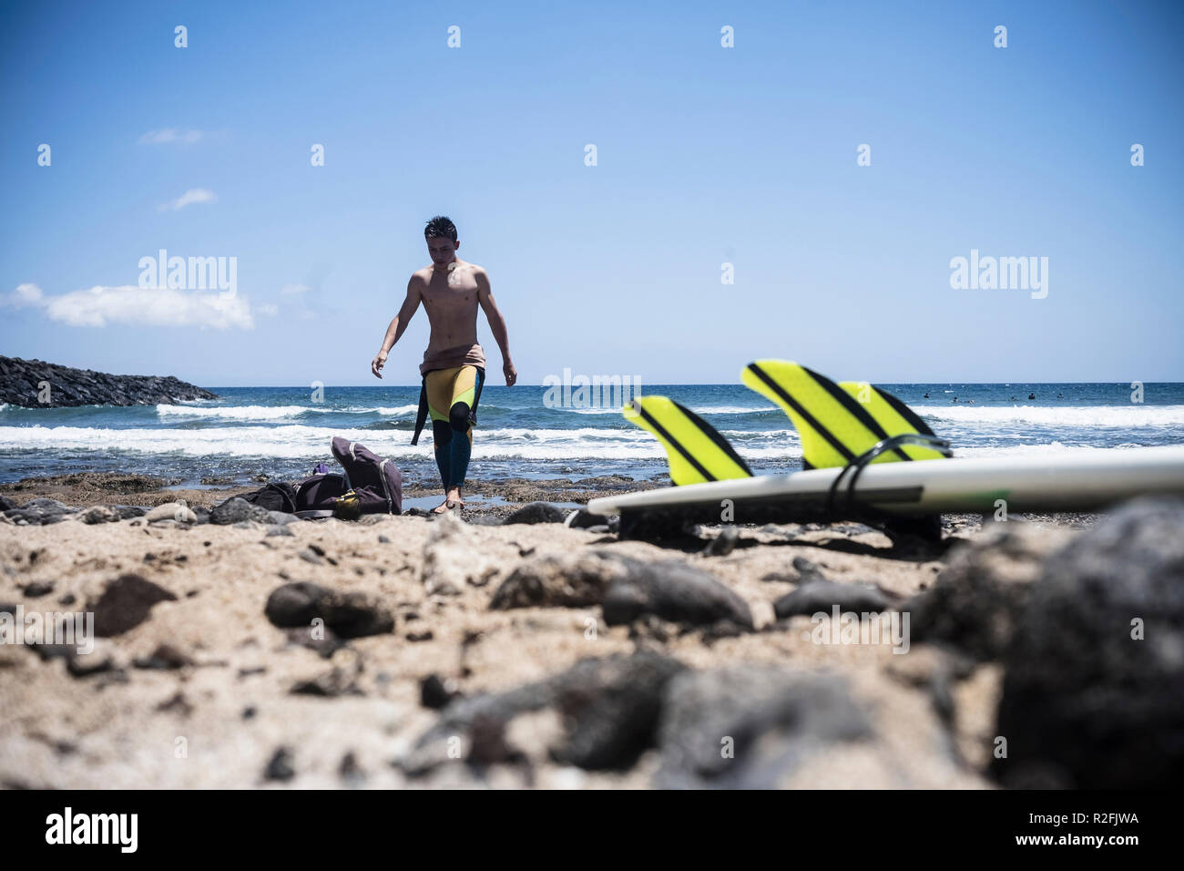 young cute teenager male surfer coming out the water after a surf session in the ocean waves. table and fins on the rocks. vacation and water sport activity concept for happy alternative people. tropical beach - Stock Image