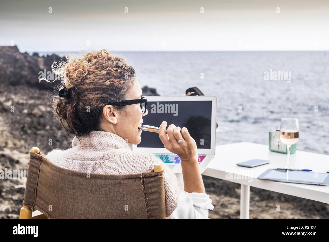 freedom and lifestyle for young woman at work in front of the ocean with no rooms and offices. laptop open and lady thinking at his career and his life. enjoying freedom and alternative work concept - Stock Image