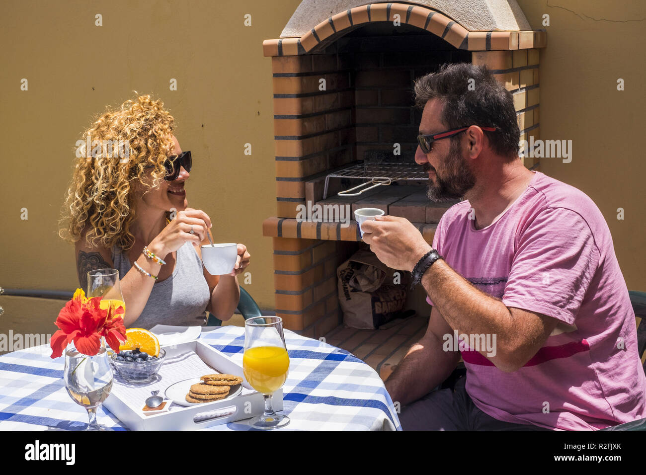 nice cheerful caucasian couple having breakfast outdoor at home near a grill barbecue. smile and spent sime good time together for adult couple. - Stock Image
