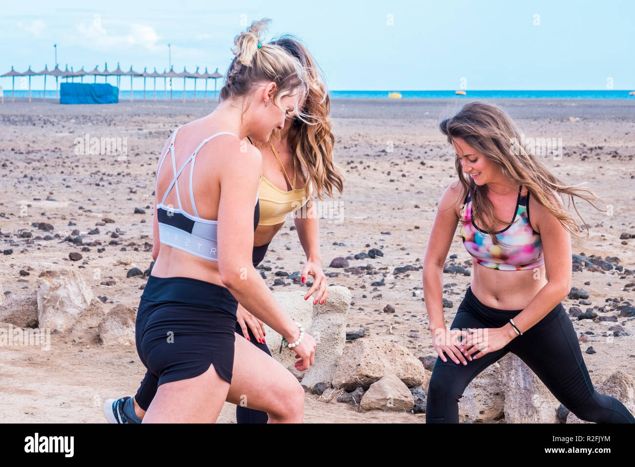 group of three of beautiful model caucasian young women doing pilates at the beach in free leisure activity. nice lifestyle healthy and in contact with the nature. ocean in background for great sport and active lifestyle - Stock Image