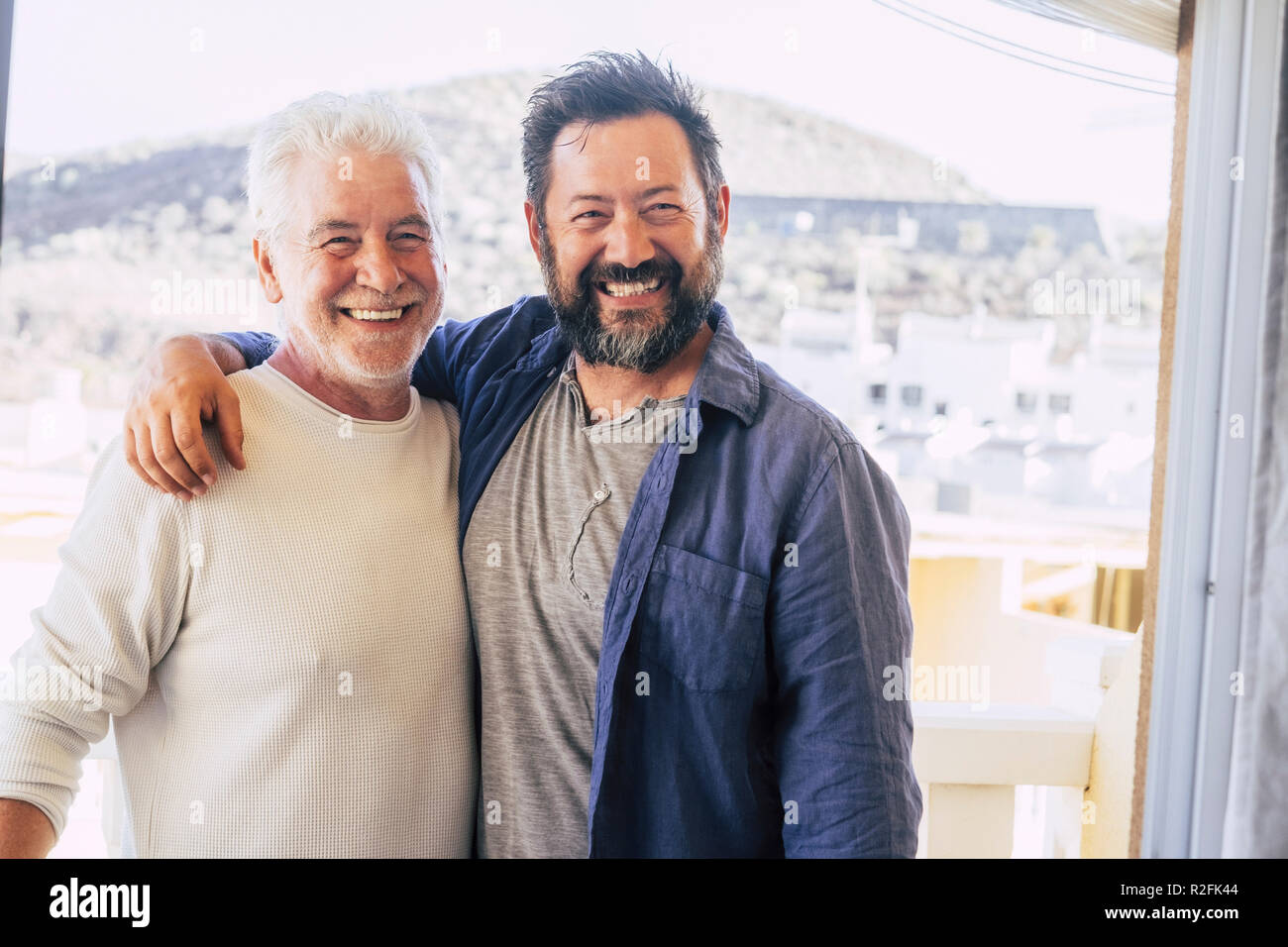couple of men hugging and stay together in friendship and relationship. father and son different ages smi.ing and look at the camera. portrait of cheerful caucasian people mixed generations enjoy life - Stock Image
