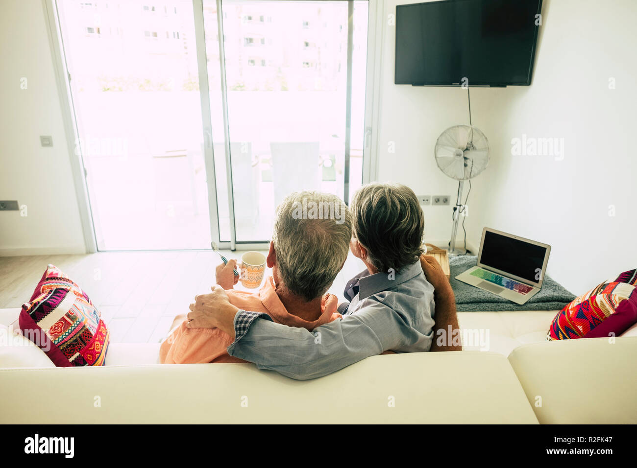 couple of senior sitting at home on a white sofa looking outside te window door to the garden. enjoying retired time relaxing together with love and satisfaction for the end of the work. laptop on the side - Stock Image