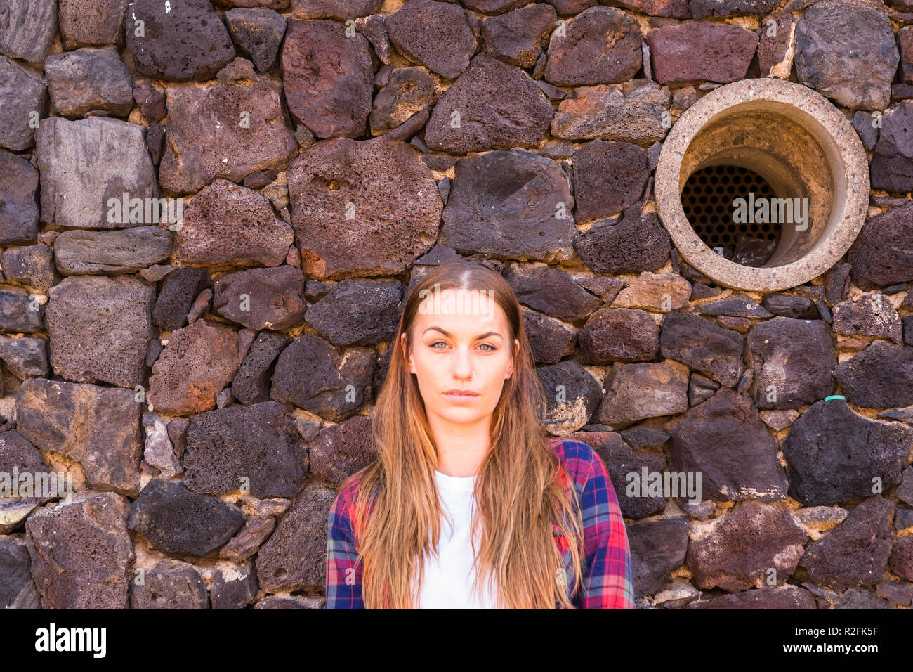 beautiful portrait of enigmatic young beautiful 30 years old woman standing under a stone wall and looking at the camera no smiling. hole in the background. long blonde hair and beauty concept Stock Photo