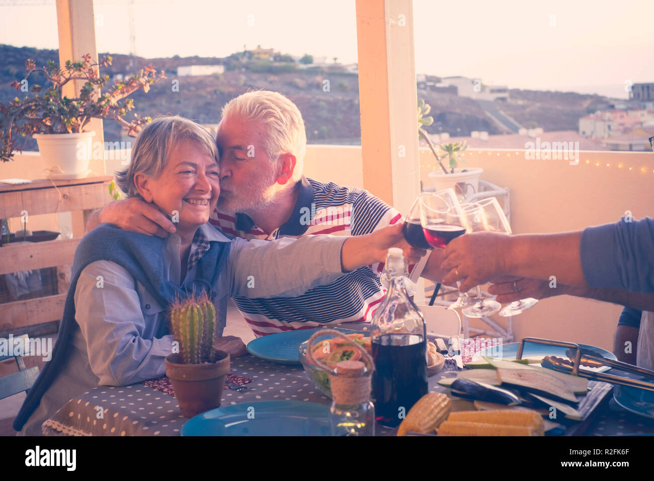 group of aged senior friends adults having dinner and doing party nice time in the rooftop terrace outdoor with wine and food. having fun and kiss  during the sunset with beautiful sun backlight and amazing view of the ocean and other roofs. - Stock Image