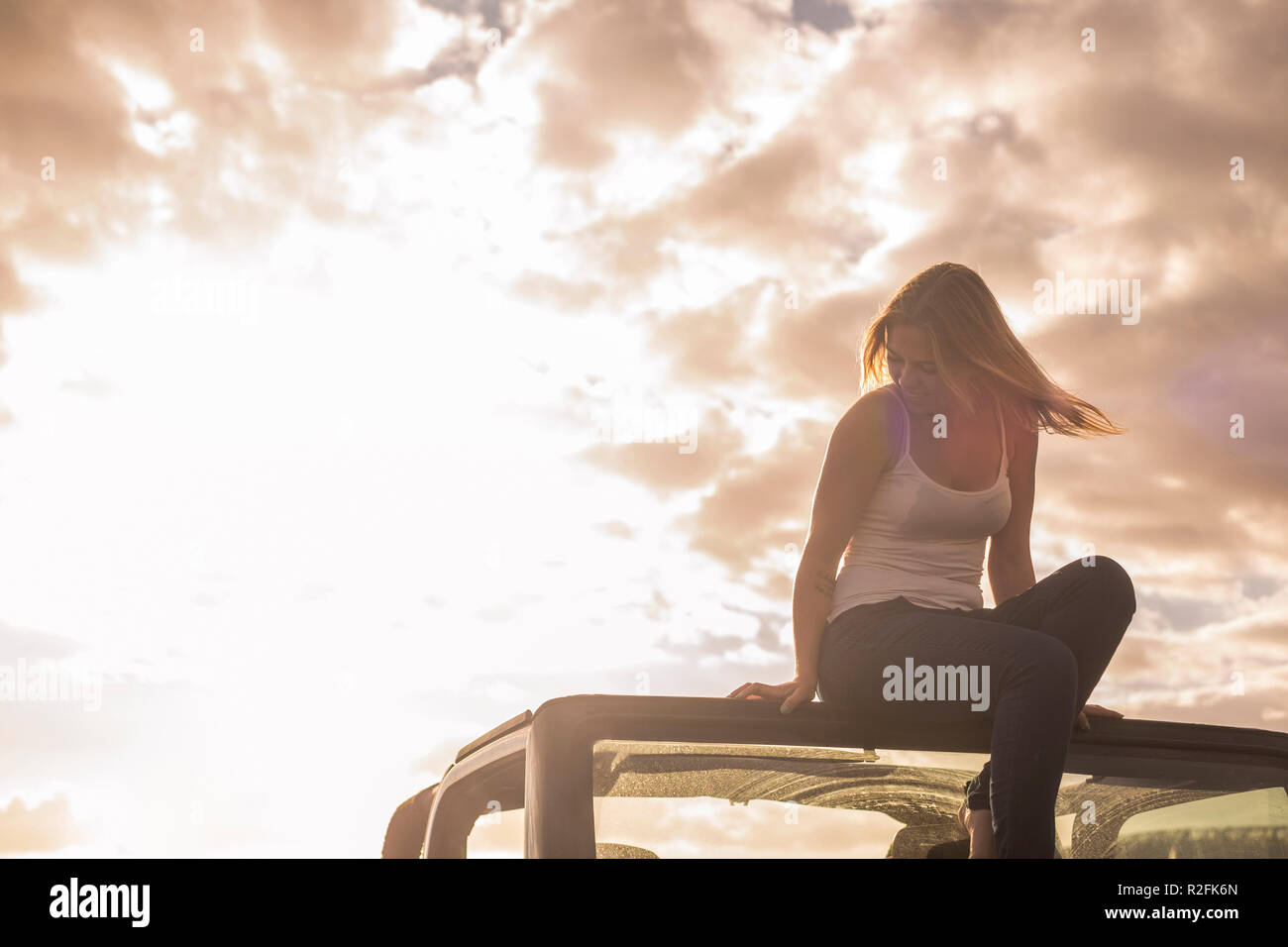 freedom and vacation concept for beautiful blonde caucasian young woman sitting down on the roof of a off road black car. Backlight and sunlight in warm tones - Stock Image