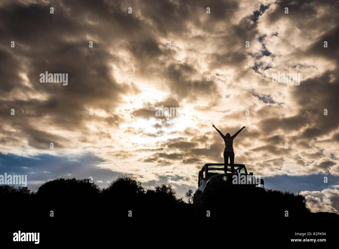 beautiful girl stand up on a off road car with amazing and great dramatic sunset over her body in silhouette.  Winner and travel destination concept - Stock Image