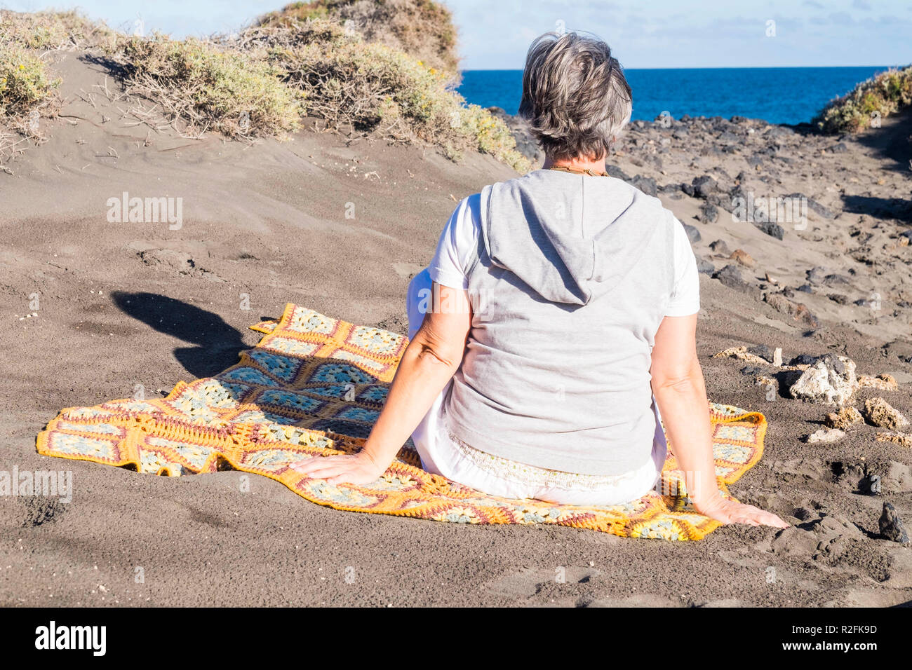 white hair old senior woman sit down and rest near the ocean. outdoor and natural place with blue sky and water - Stock Image