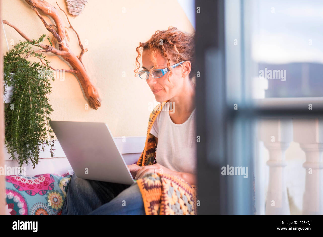 free work style lifestyle independent for cute beautiful caucasian woman work and write a book at laptop on the terrace outdoor at home. modern kind of work concept. - Stock Image