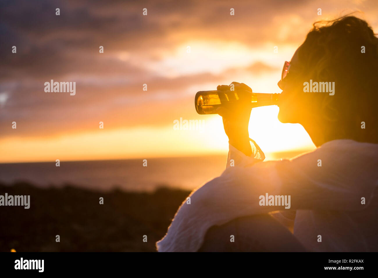 beautiful young woman middle age drink a beer with satisfaction during holiday or celebration for a success at work or in life. day end with an award made by amazing sun and colors. - Stock Image
