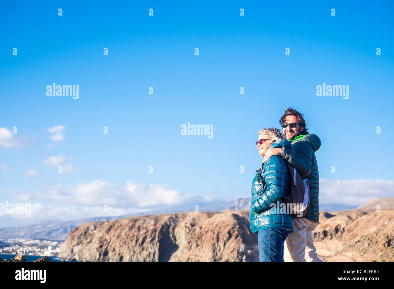 Mother with white hair and a 45 year old son spend time together smiling, surrounded by unspoiled nature. Between sea and mountain - Stock Image