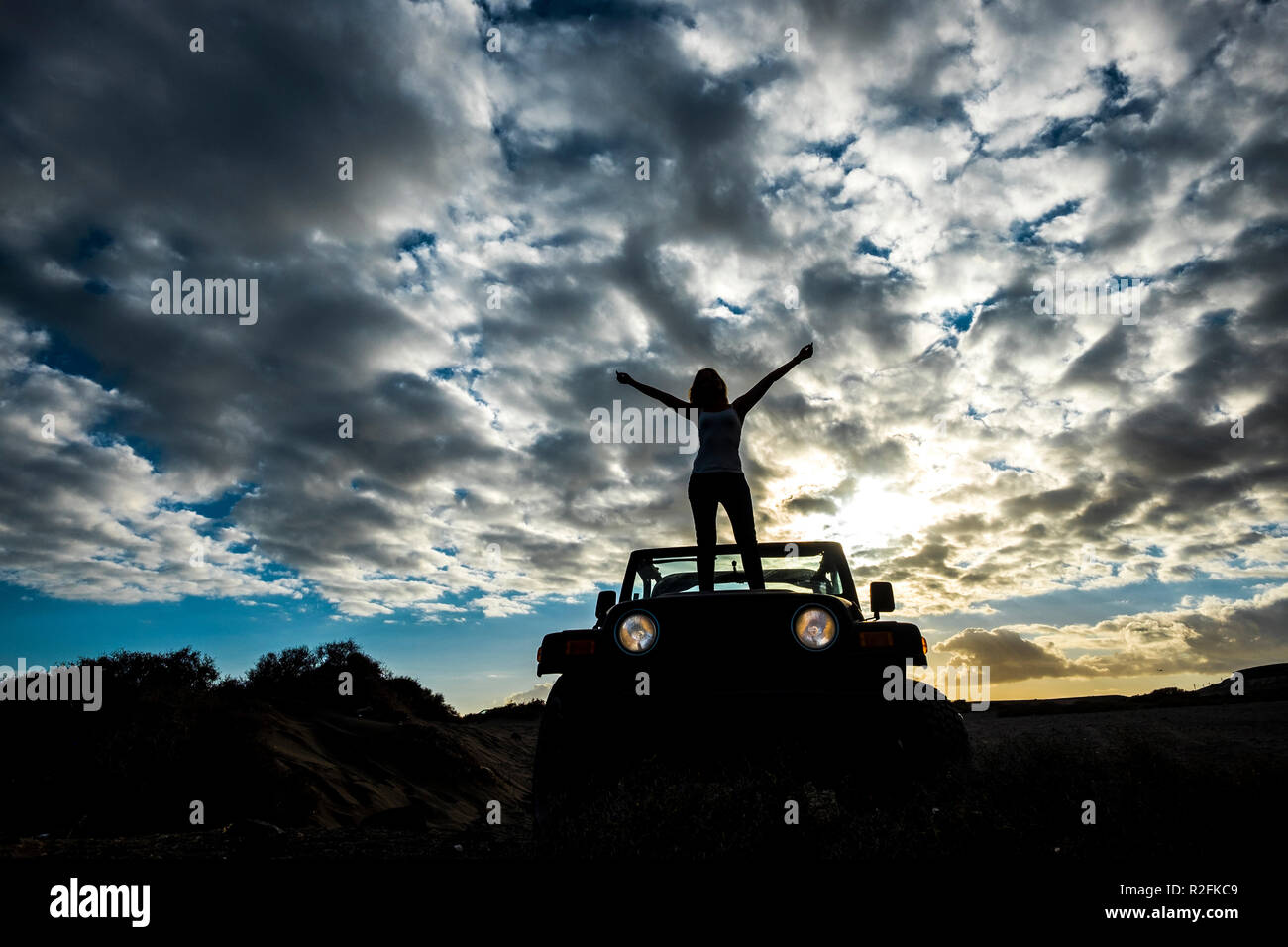 winner and satisfaction concept. traveler cute girl with nice body standing up on the front of the car with amazing sunset on the background. Tenerife location. - Stock Image