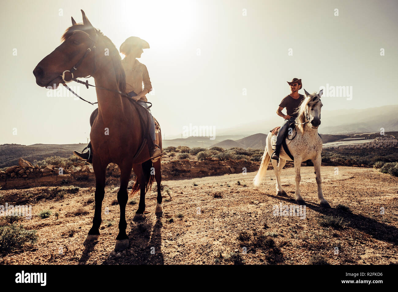 couple of horses and cowboys male and female ride free in the nature at the mountains in tenerife. lifestyle and alternative works or leisure activity concept for man and woman Stock Photo
