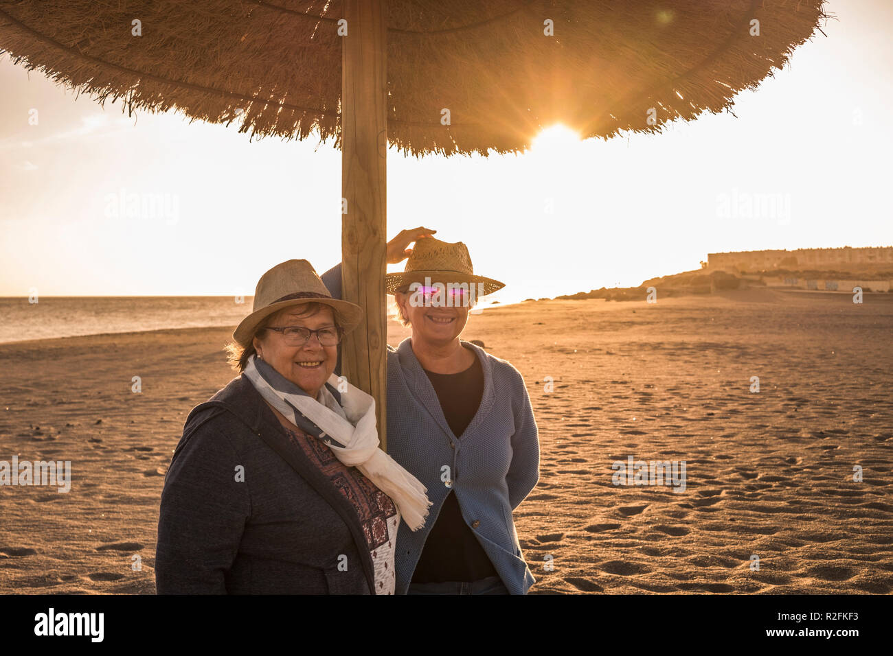 two senior women with hats on the beach under an umbrella. Sun Backlight of sunset. Leisure time in the summer in Tenerife. - Stock Image