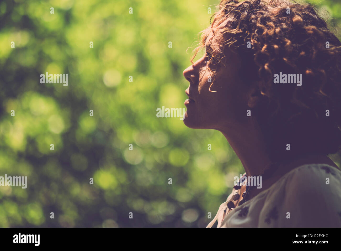 warm tones for a beautiful woman looking in front of her with a green natural bokeh in background - Stock Image