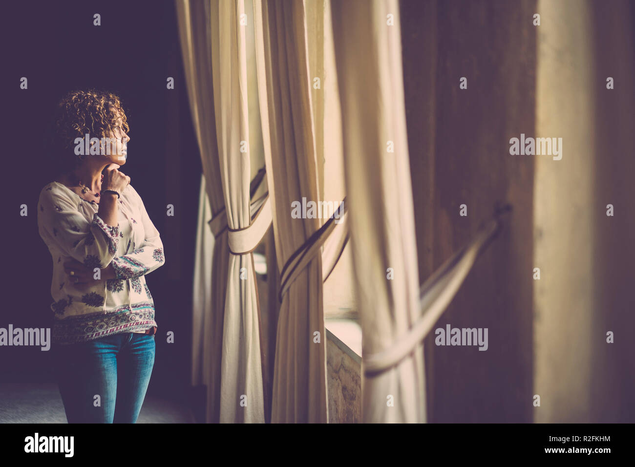 beautiful woman look outside in an ancient house with the light on her face. - Stock Image