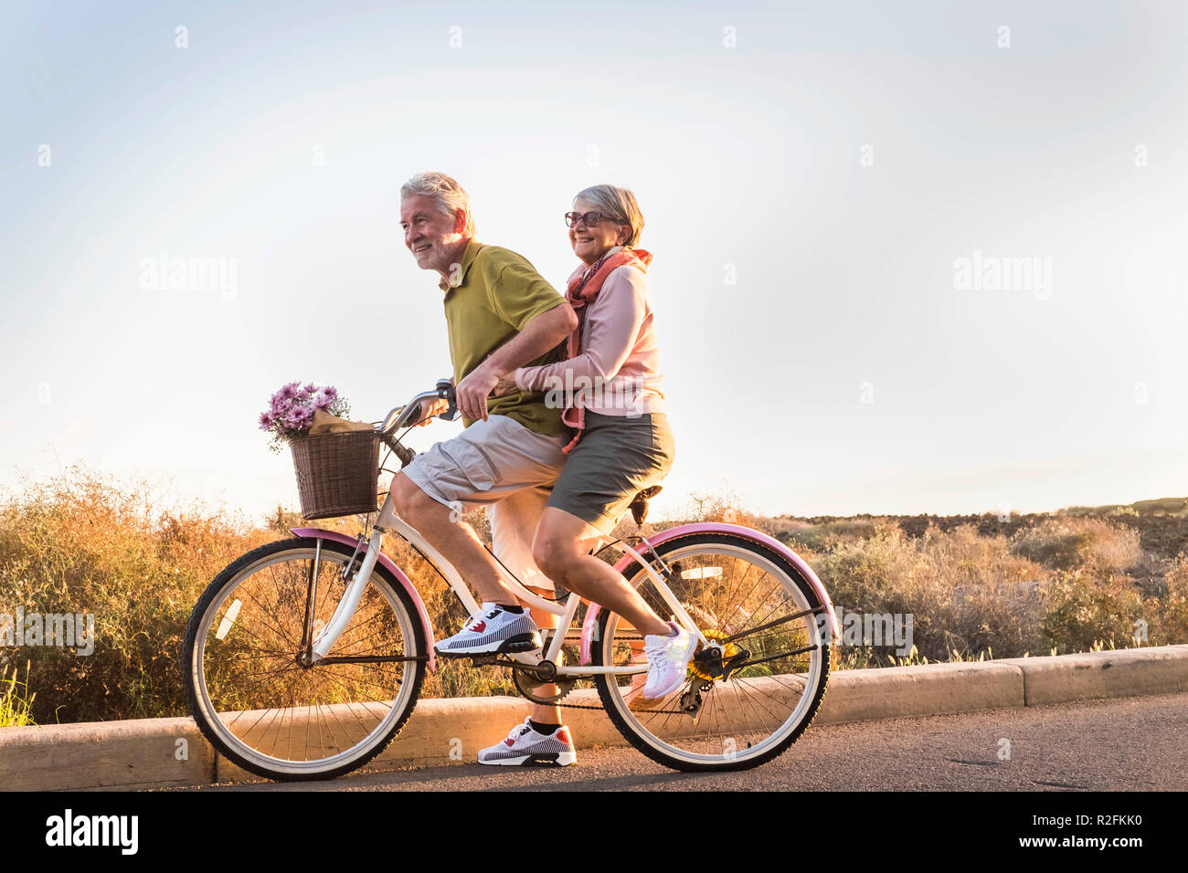 two senior man and woman together on  an old bicycle outdoor activity. happyness and freedom from work concept. sunlight and smiles. - Stock Image