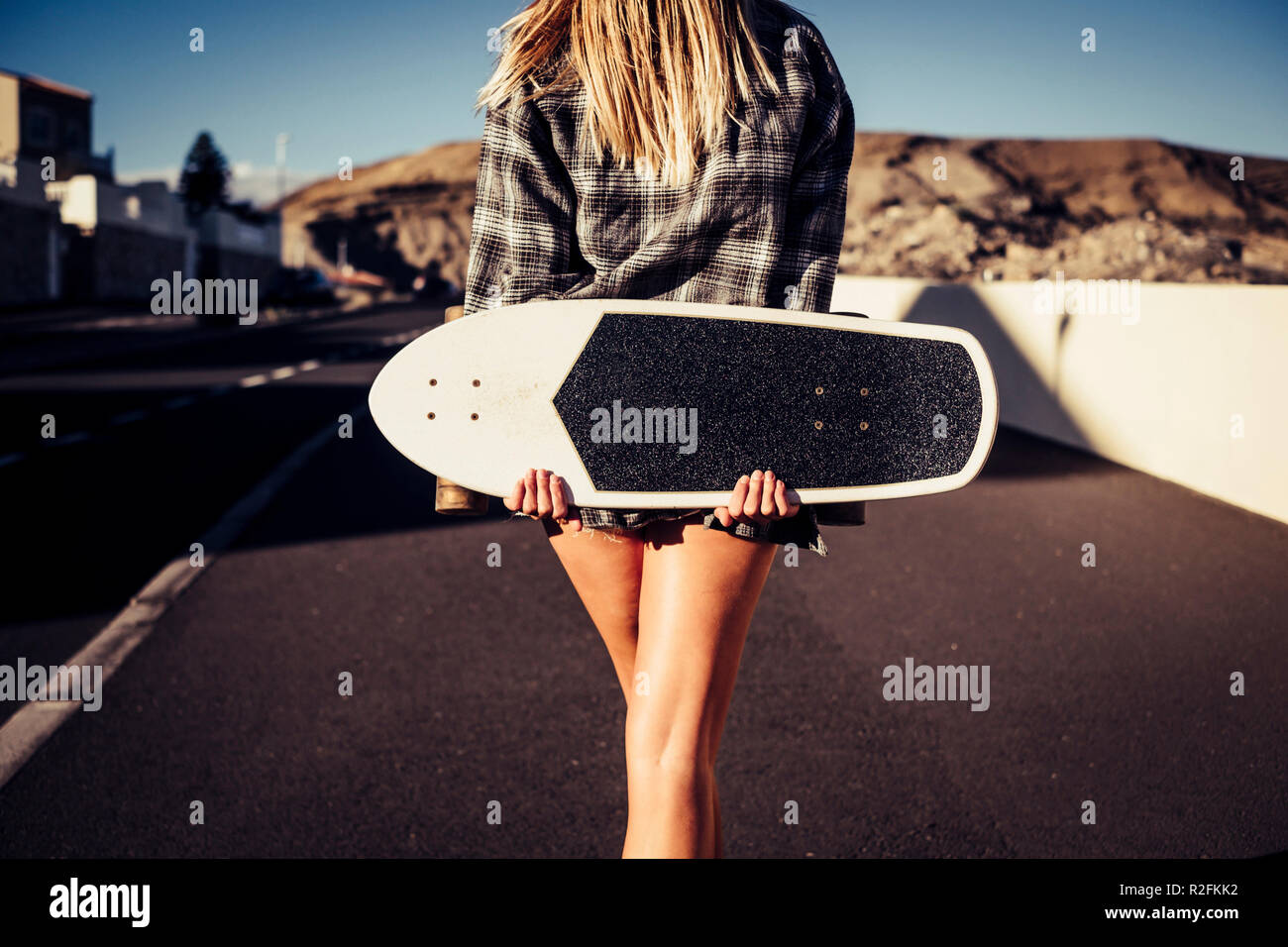 freedom and alternative lifestyle outdoor concept for beautiful blonde young woman walking on the street with skateboard and wind in the hair. enjoying life and day time. warm colors. - Stock Image