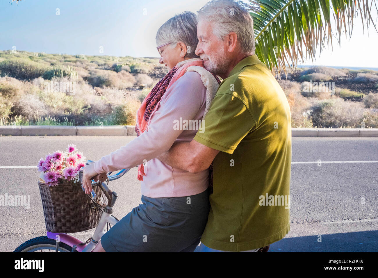 nice and cute couple of adults models playing on the same bike outdoor. leisure activity for happy retired people on holiday in tropical place near the ocean. tenerife vacation concept and smiling people with palm tree - Stock Image