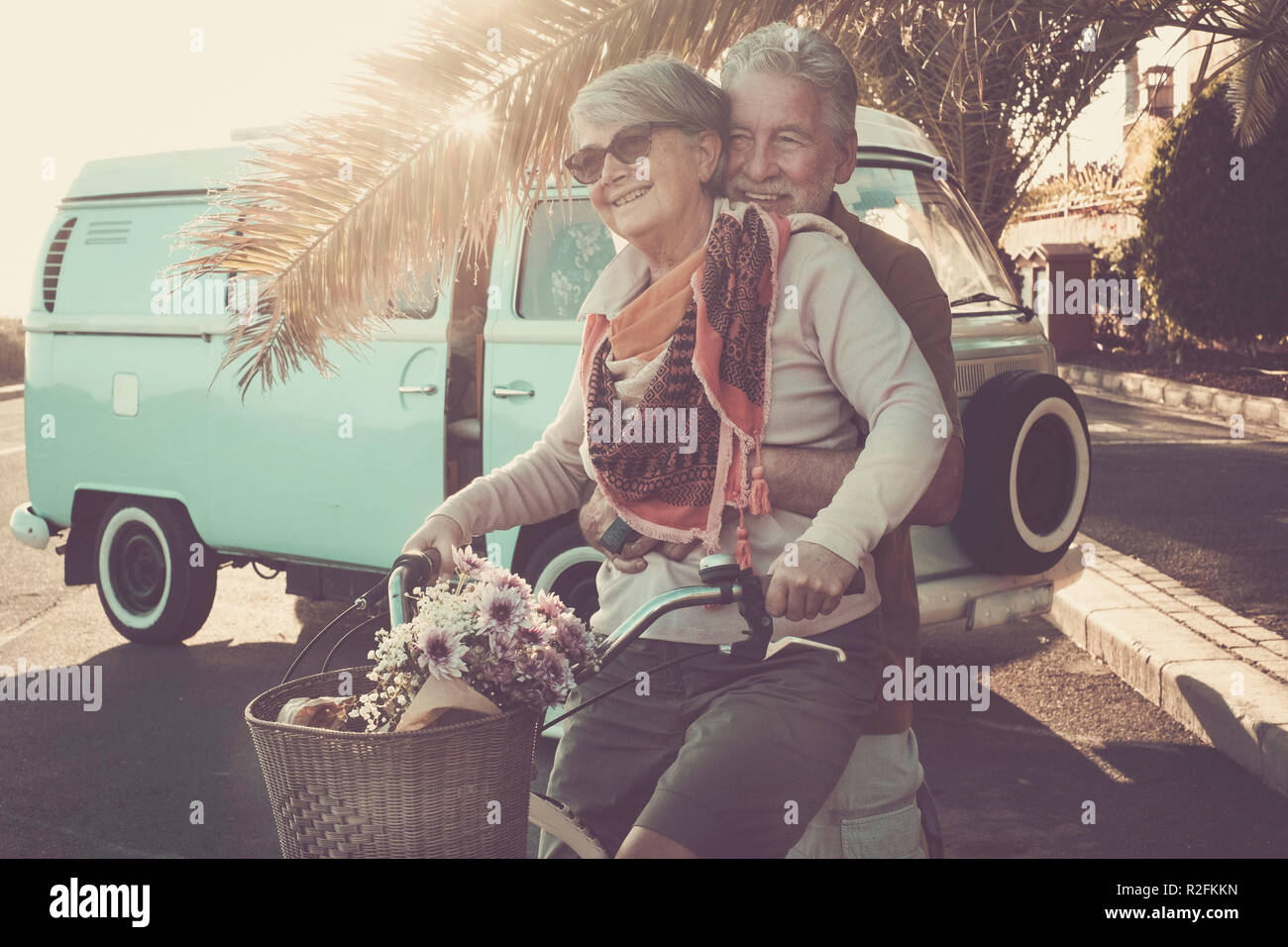 two senior aged couple go bike together in traveler vacation activities. playing and live a funny lifestyle. sun in backlight and old vintage van. - Stock Image