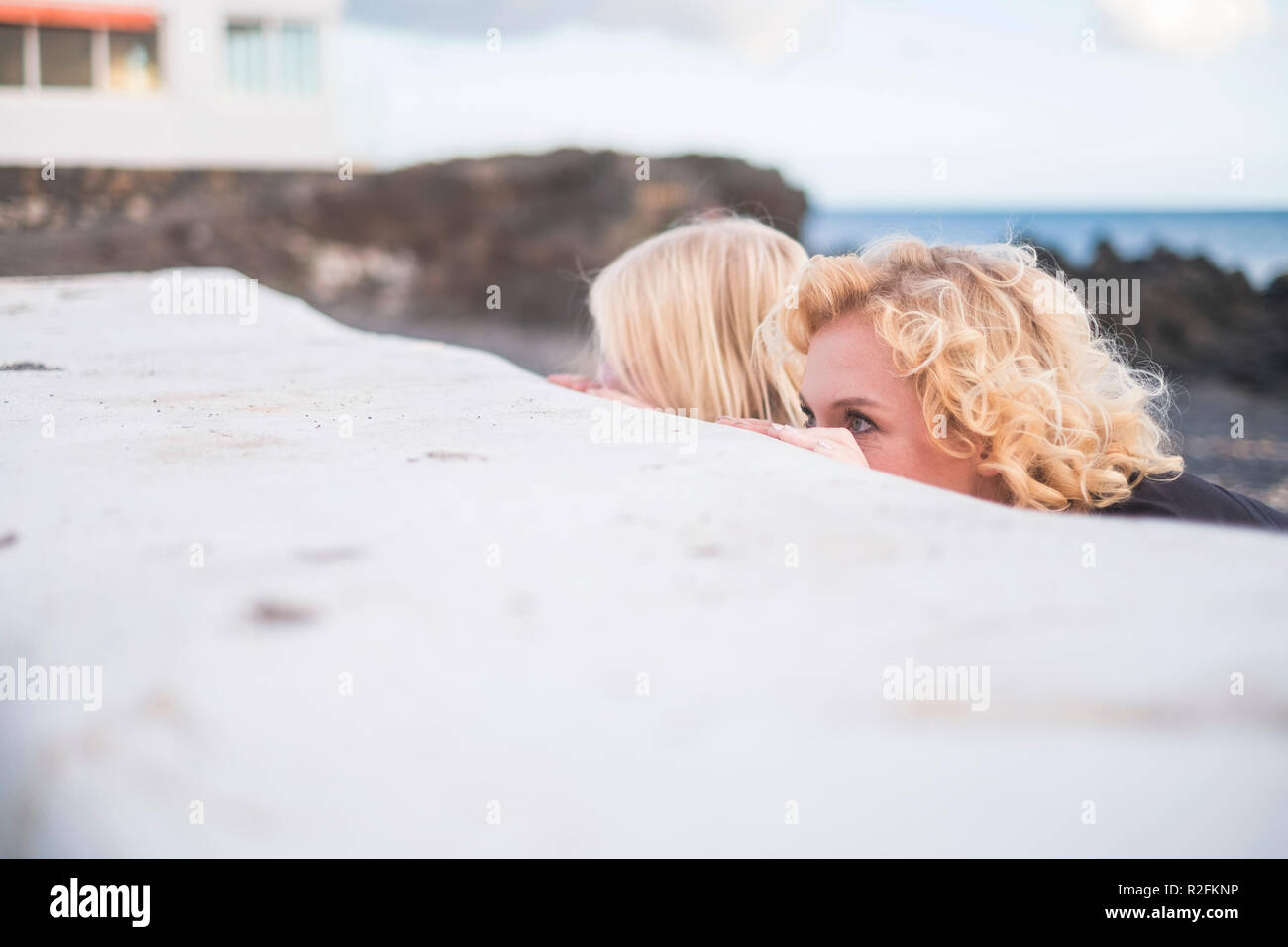 playful leisure activity outdoor with young mother and son hiding and playing togetherbehind a white wall and enjoying the summer time together - Stock Image