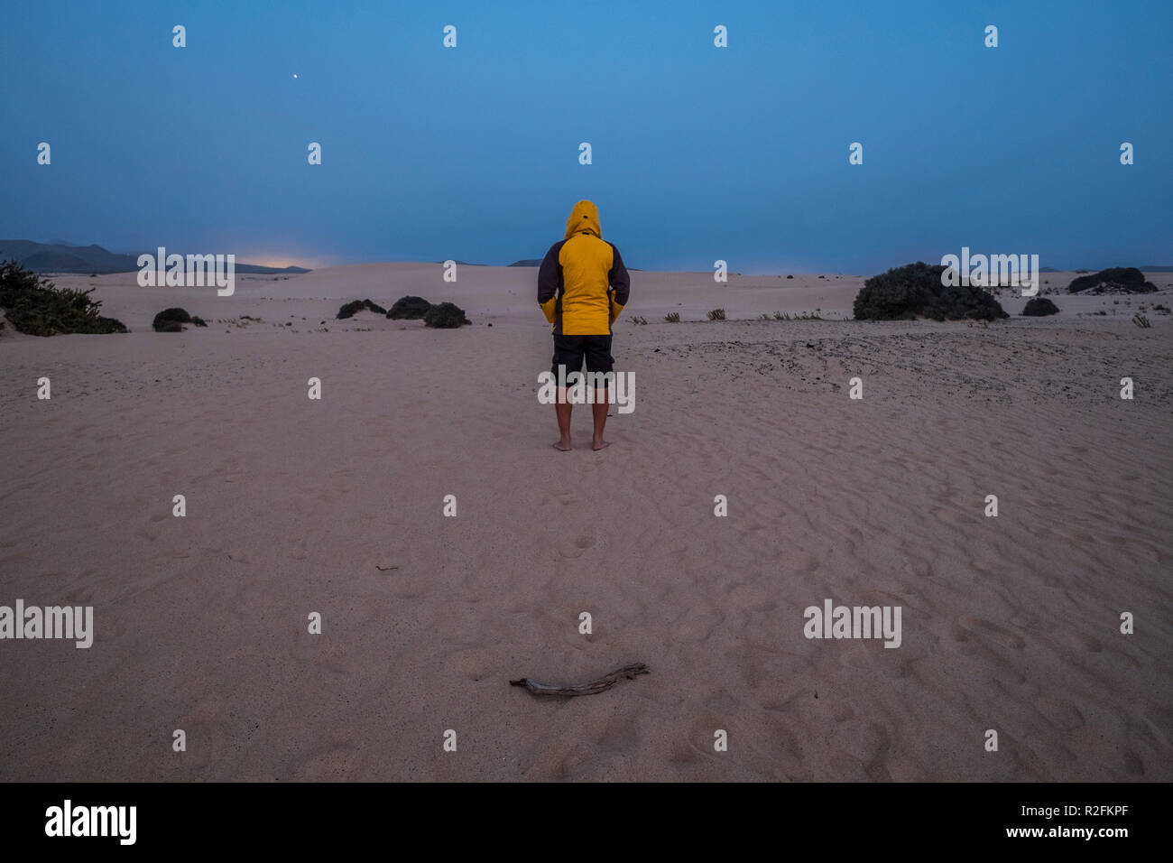 single man with yello jacket wait and stand in the middle of the desert of corralejo fuerteventura by night in the evening. cold and enjoying the nature around wth nobody for alternative vacation and lifestyle concept - Stock Image