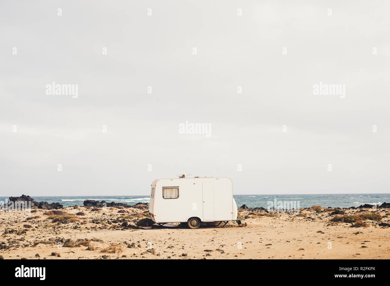 really alternative lifestyle in contact with the nature and yourself living in the middle of nowhere with a little tiny house caravan parked on the coast with ocean waves view. independence and wild life. fuerteventura. - Stock Image
