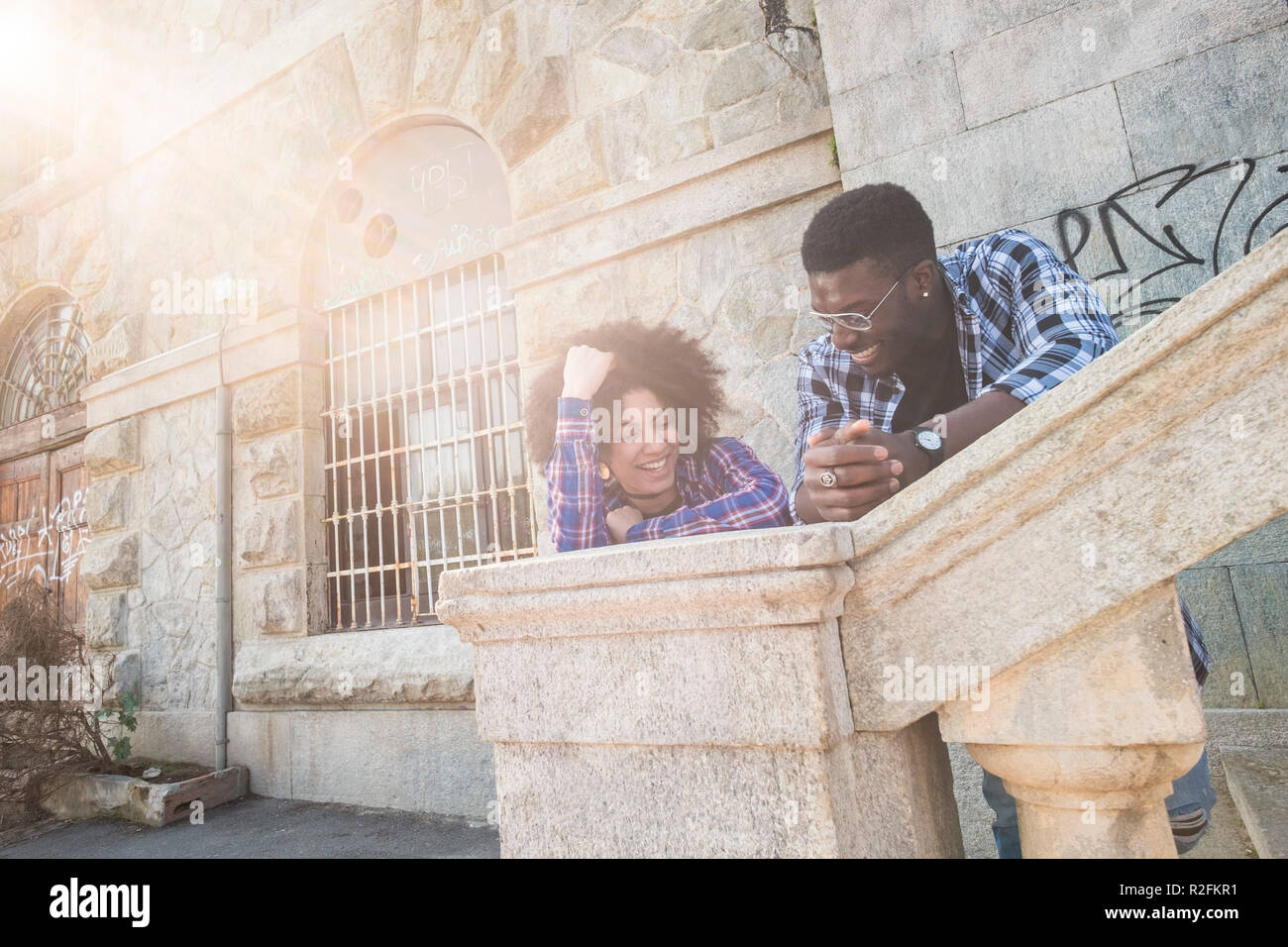 hipster young teeanger couple heterosexual man and woman enjoying the day together with smile and joy speaking and spendig time. attractive models in urban ancient city. italy with afro races - Stock Image