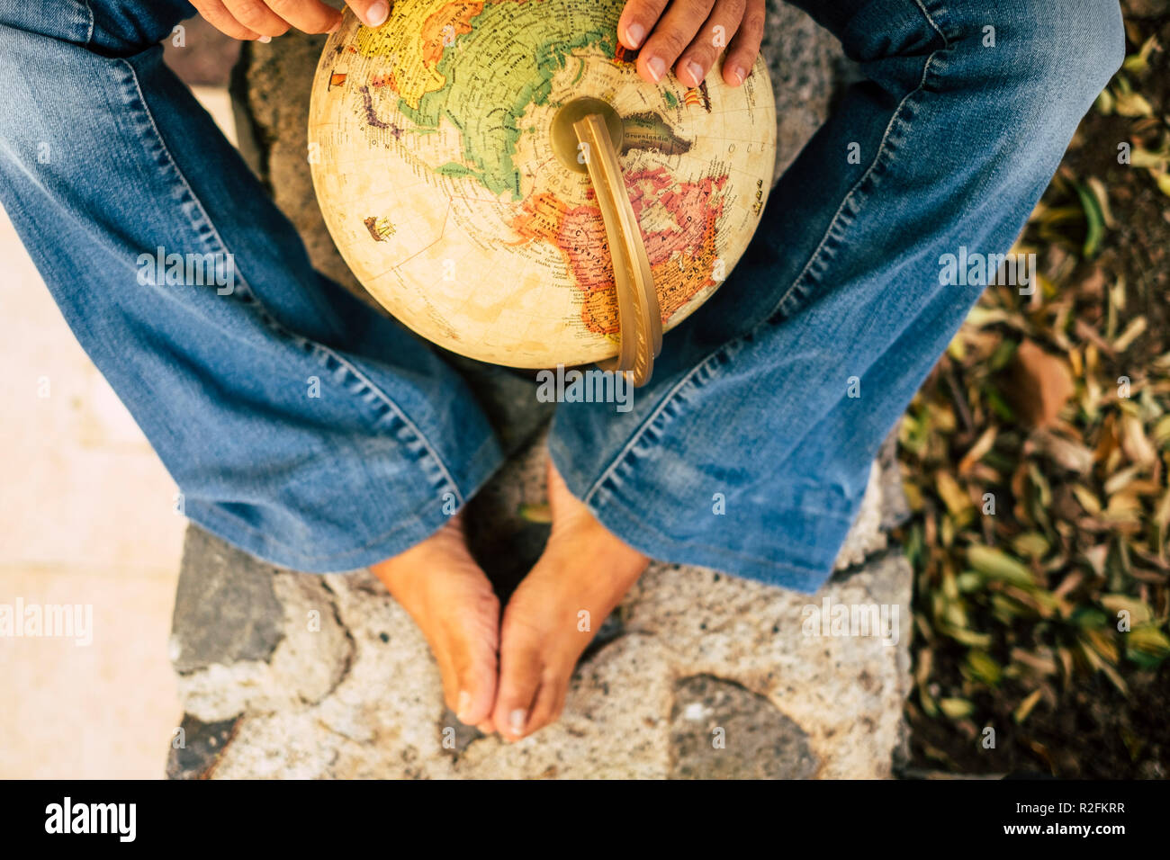 traveler caucasian legs and hands with a earth globe sphere in the middle choosing the next trip journay vacation destination rounding the map.  travel explore and young modern people concept wanderlust - Stock Image