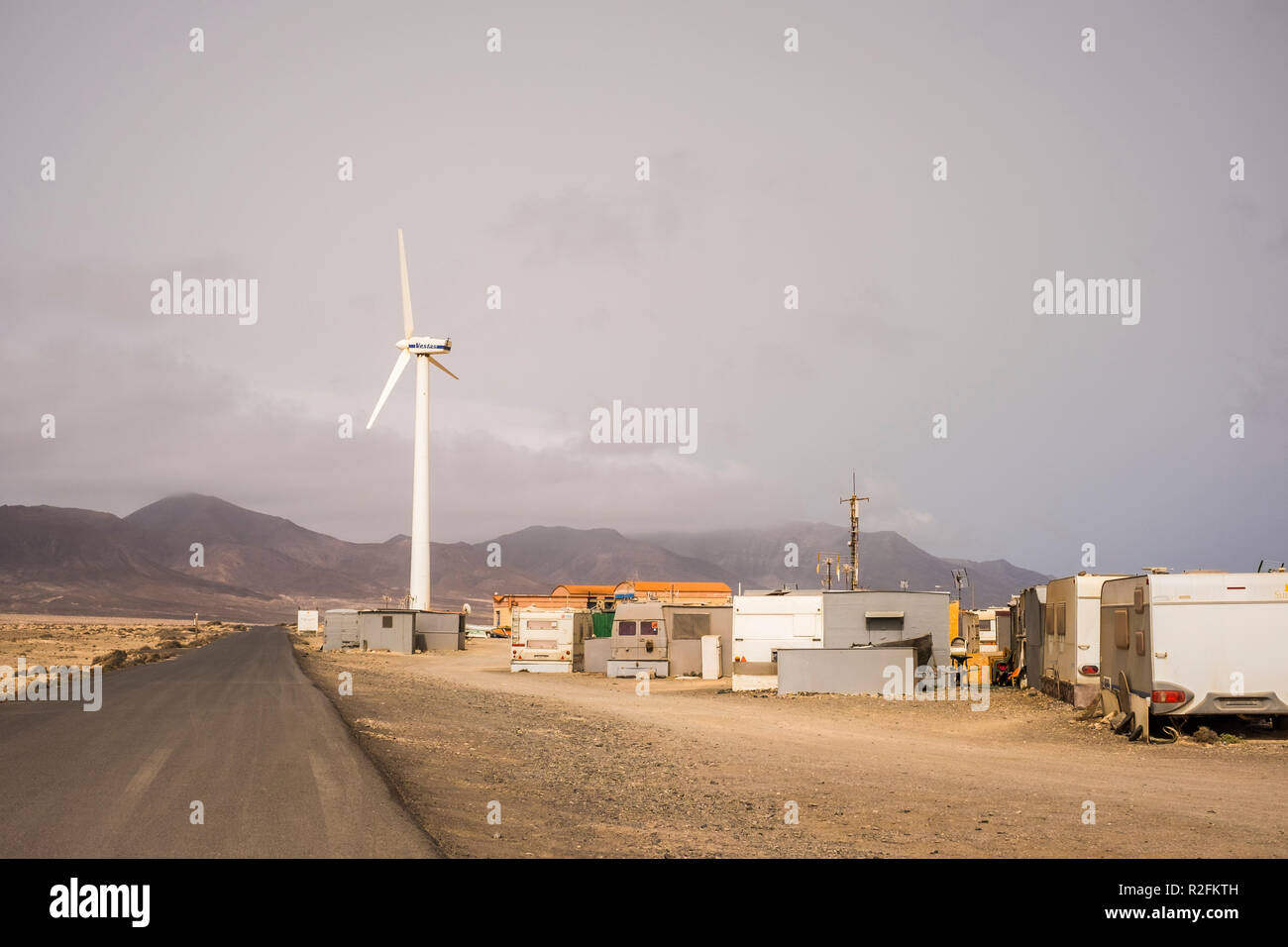 independent little town with houses and caravan hippy and out of siciety lifestyle. one road to come and go and one windmil to produce the energy they need to live there or survive. no comfort zone, out of the box life Stock Photo