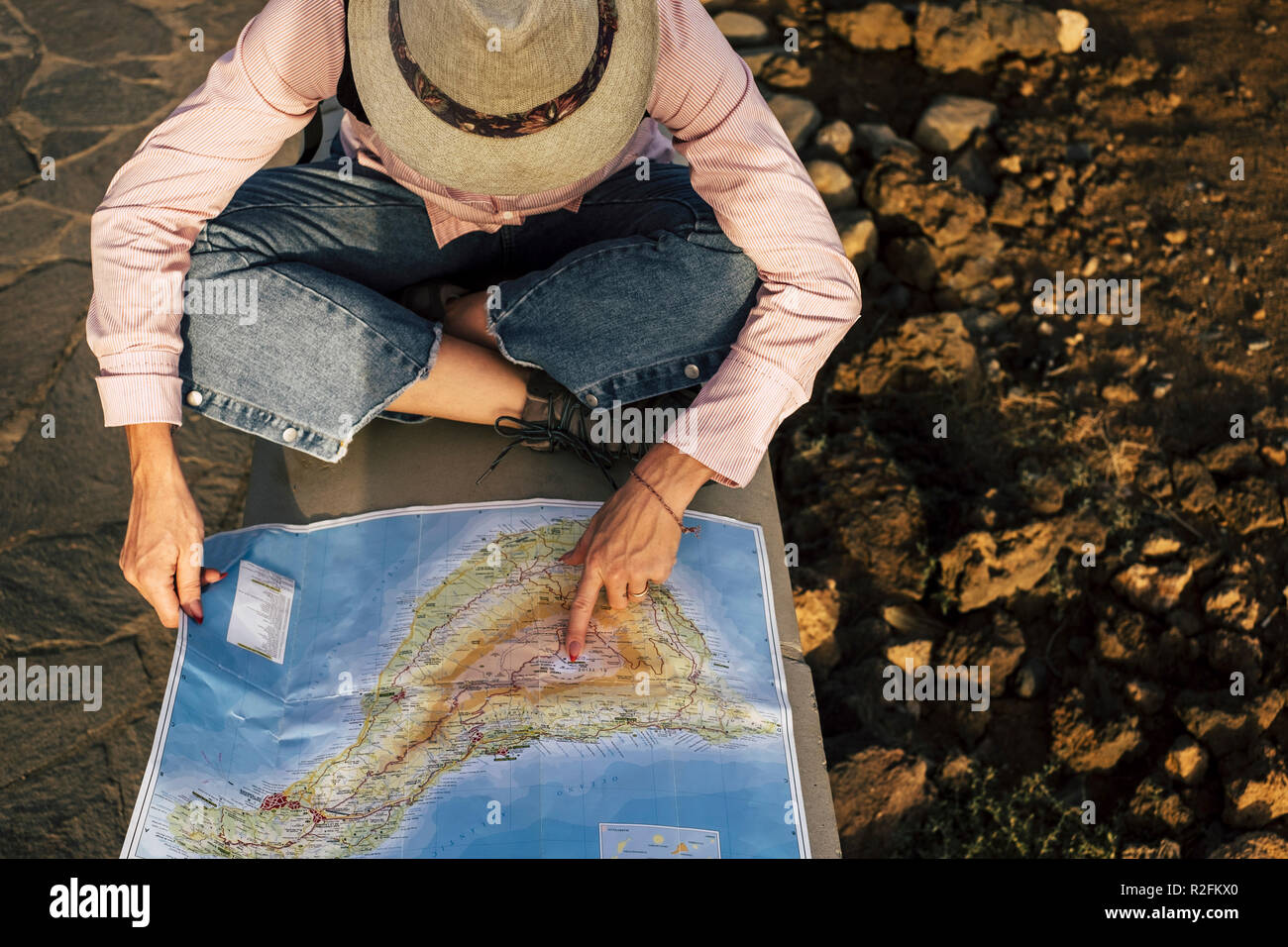 above aerial view of nice adventurer woman looking on the map for her next stop and destination place loceation. tourism and alternative way to travel and discover the world. wanderlust and happy lifestyle concept for milennial people - Stock Image