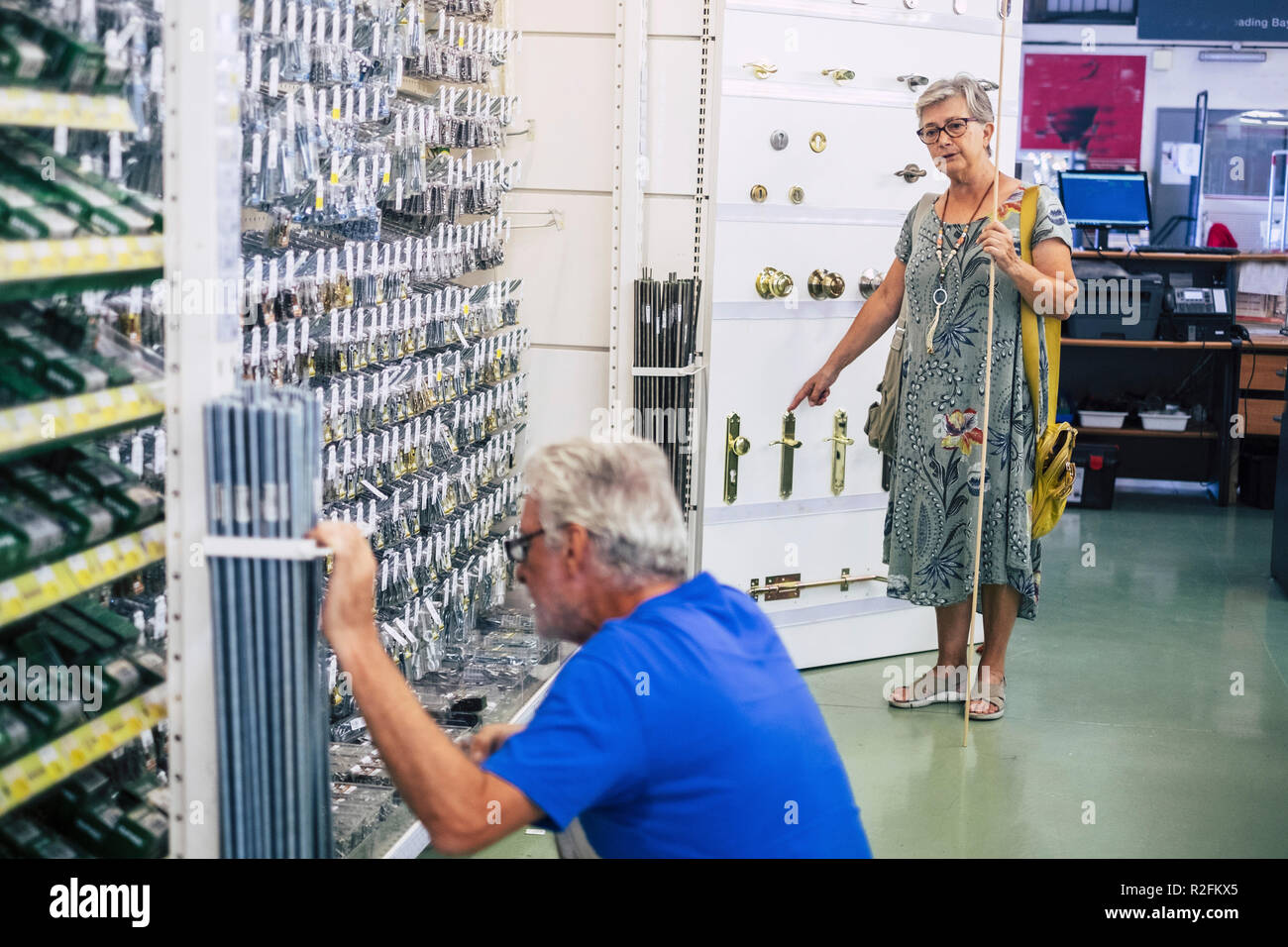 Senior adult couple in hardware shop together looking for and choosing stuffs to build or repair furnitures or other things at home. mature people  working and doing shoping together - Stock Image