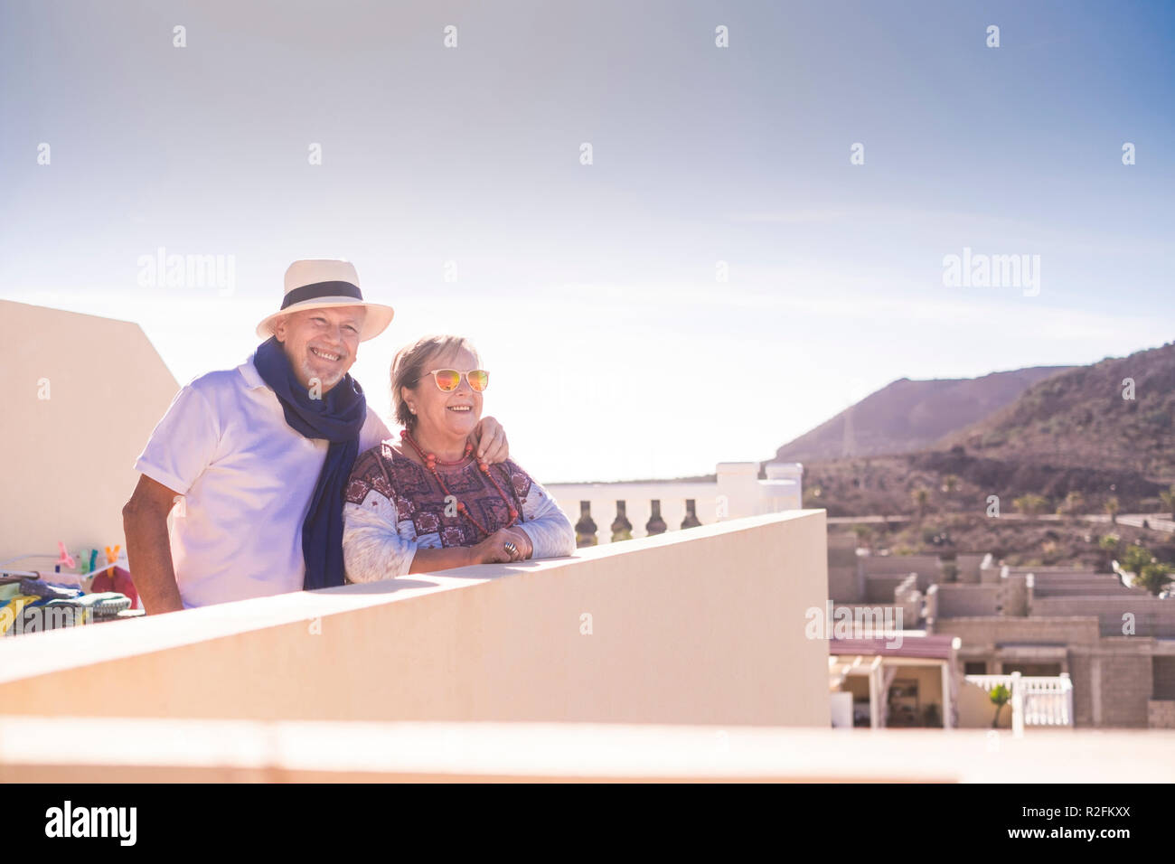 senior couple having some time on the rooftop at home with view on other buildings in contruction and mountains. sunlight and plants and nature outdoor. - Stock Image