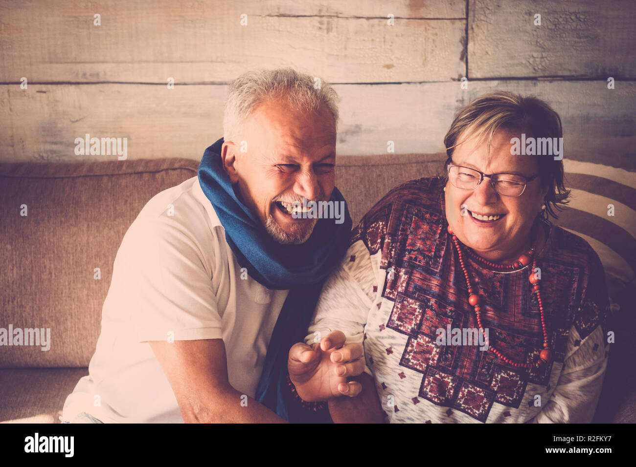 senior man and woman having a lot of fun at home sitting on the sofa. Both laugh together. Home life concept. Brown and warm colors - Stock Image