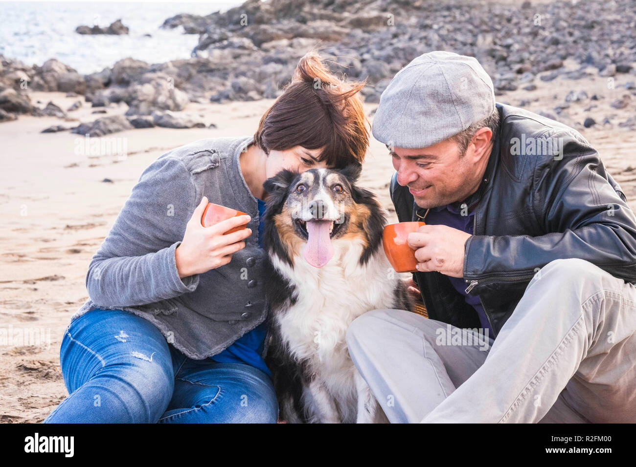 family with a border collie dog doing pic nic activity on the beach in vacation, summer lifestyle with friends concept. old style and vintage filter. tea break time - Stock Image