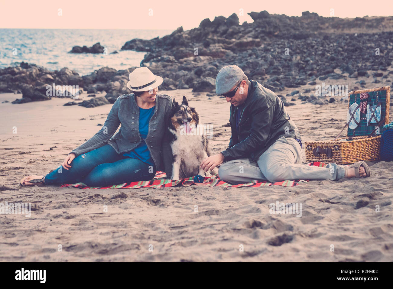family with a border collie dog doing pic nic activity on the beach in vacation, summer lifestyle with friends concept. old style and vintage filter Stock Photo