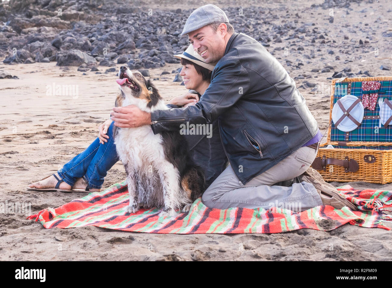 freedom and leisure pic nic activity on the beach for an alternative family group of friends two person and a nice dog. everybody have fun outdoor in vacation Stock Photo