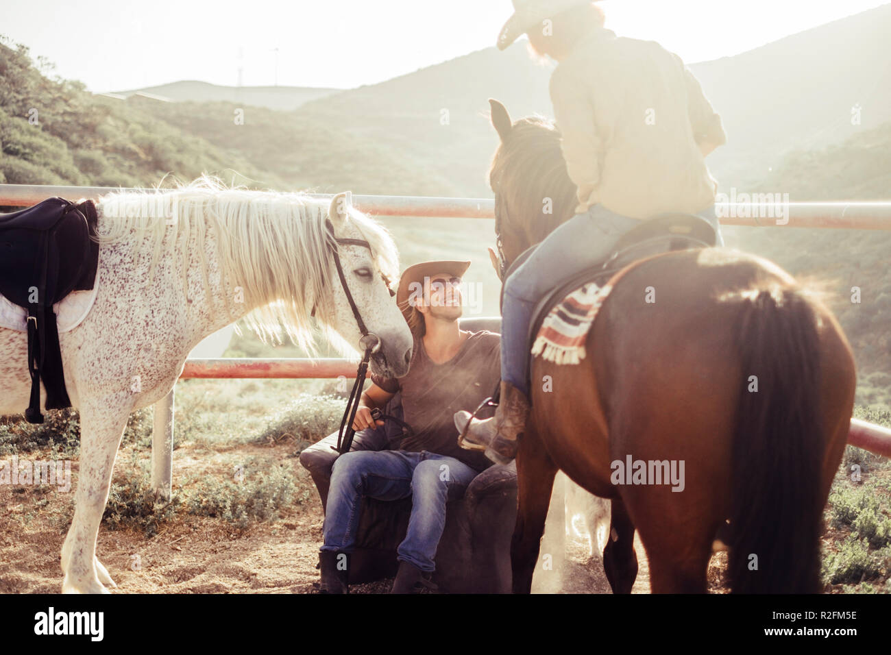 Countryside And Horse Farm Daily Scene With Sun And Backlight Two Horses And Two Rider Man And Woman Smile For A Beautiful Day In The Nature Friendship And Animal Therapy With Cowboy