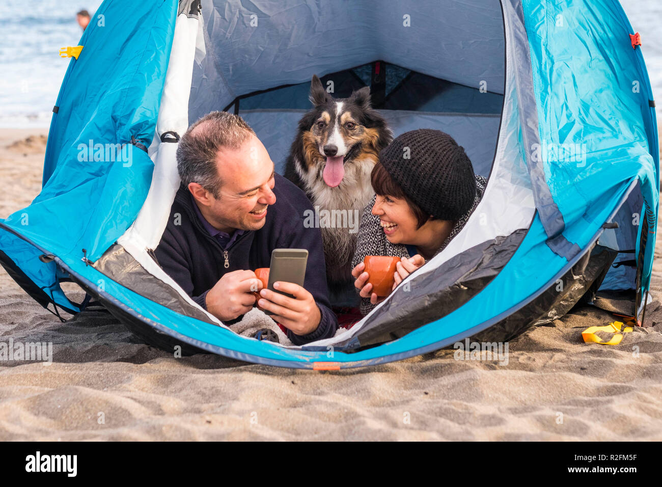 nice beautiful paople with cute puppy inside a tent using cellular phone to send message or take picture. beach camping freedom alternative vacation in tenerife with your best friends dog - Stock Image