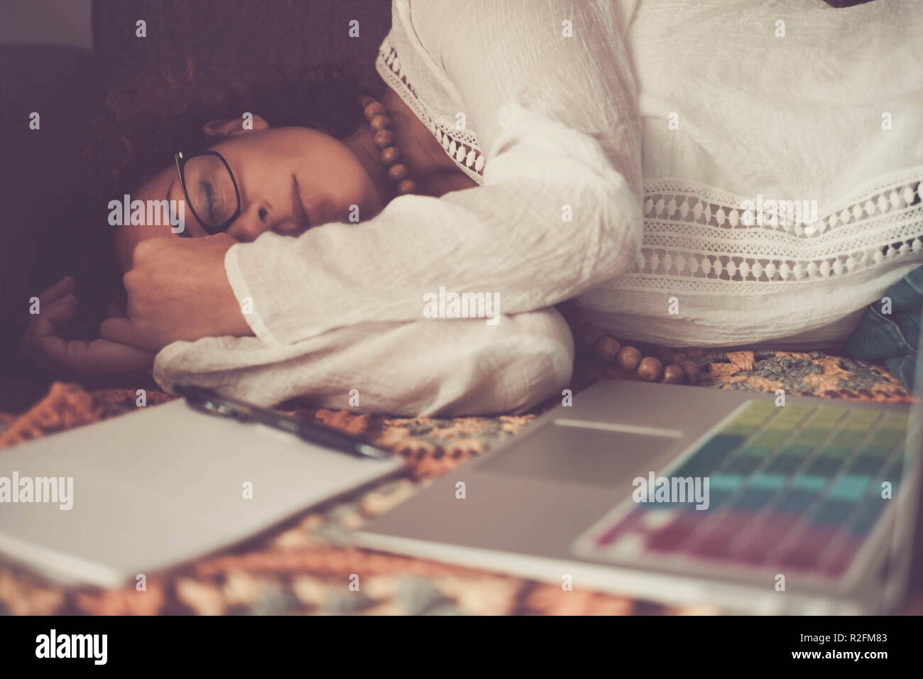 lonely beautiful caucasian woman sleep after a strong hard work at home with laptop. no hours problem working at home instead that an usual office. alternative choice lifestyle for freedom and independence - Stock Image