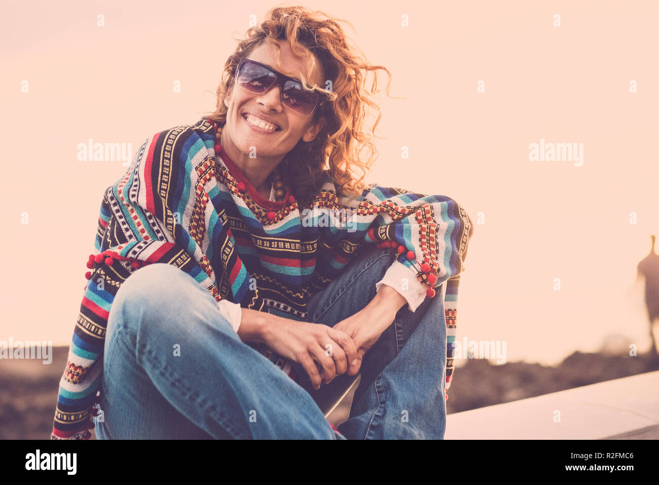 nice cute lady with swirl hair smiling at you while sit down near the ocean coast. poncho and hippy clothes to represent freedom concept. vacation style in magic atmosphere. wanderlust. - Stock Image