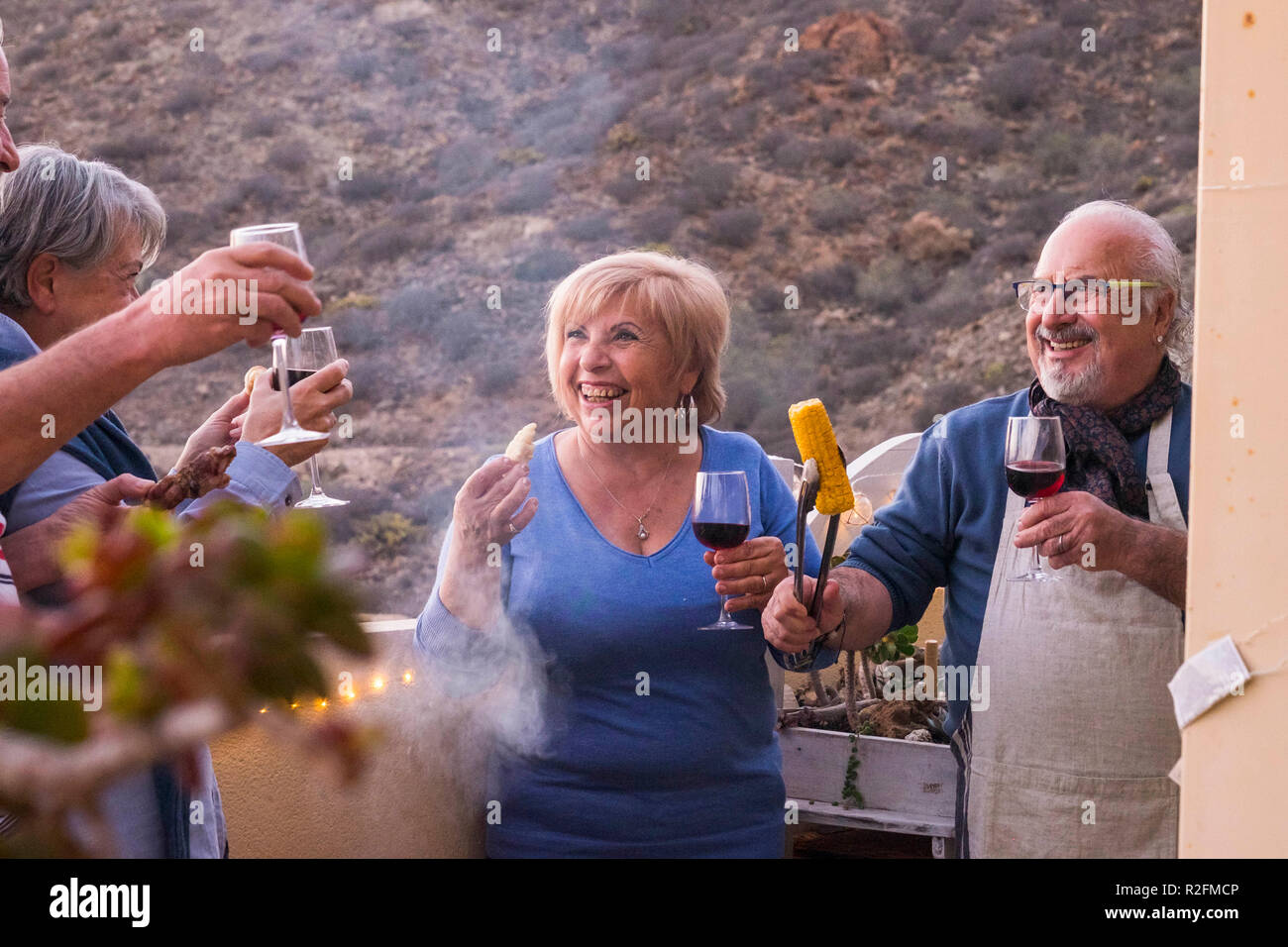 rooftop terrace bbq for four senior aged men and women staying together outdoor on the terrace. mountains and nature background for nice activity happy - Stock Image