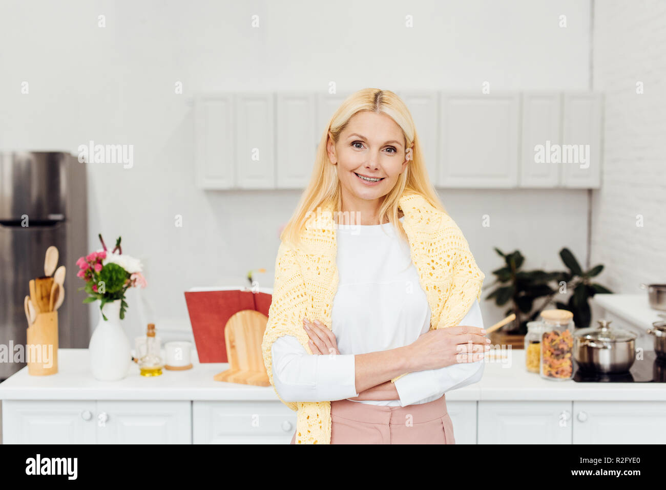 smiling blonde woman with arms crossed standing at kitchen - Stock Image