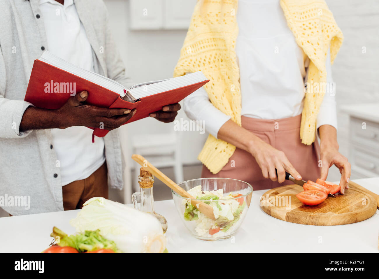 cropped view of interracial couple cooking dinner together at kitchen Stock Photo