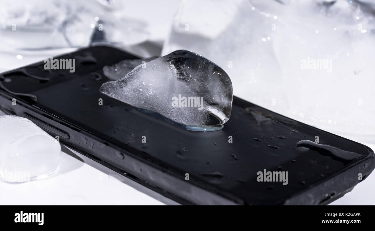 Black smartphone frozen in ice. Abstract object photo. - Stock Image