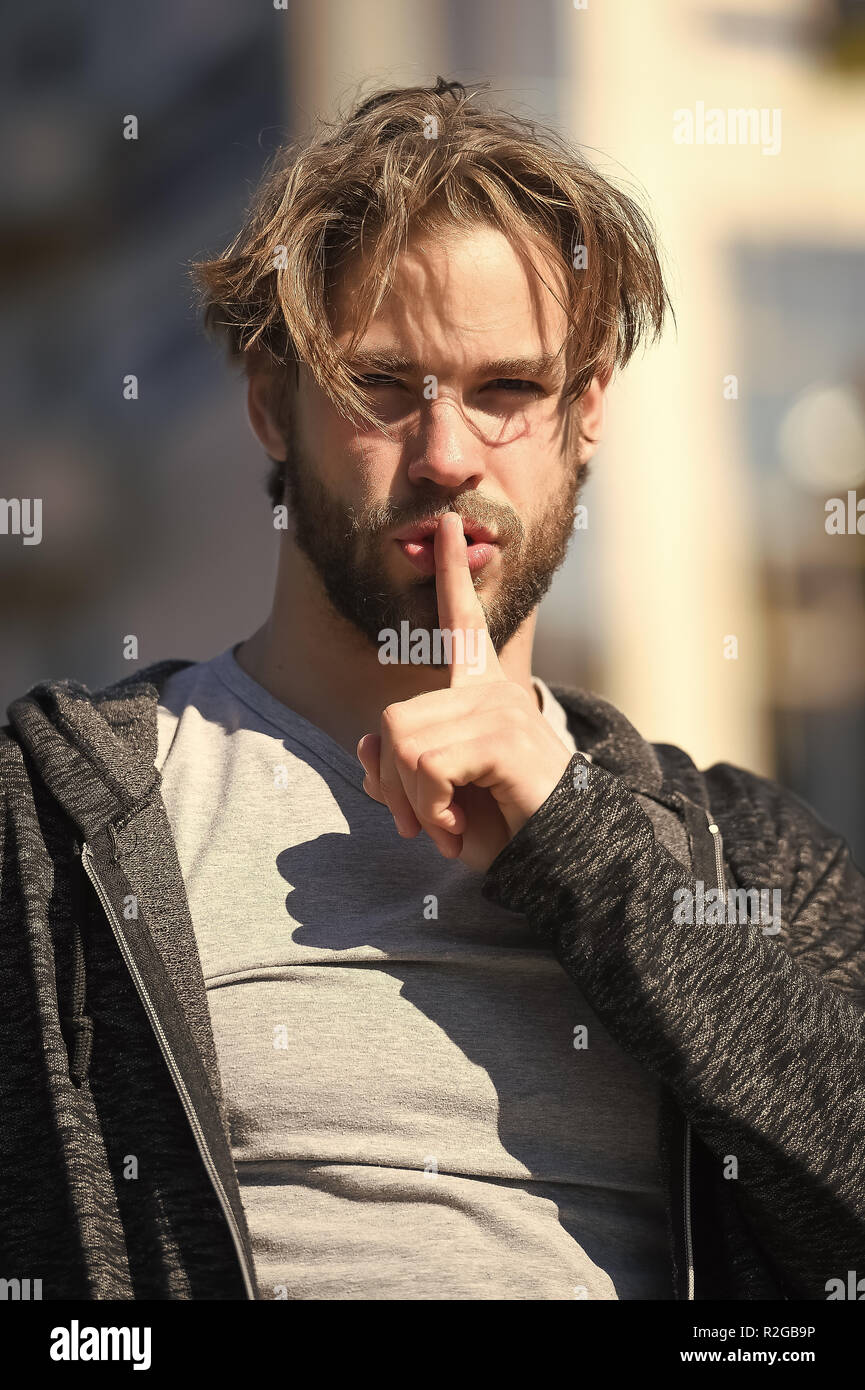 Macho with hush finger on lips, bearded face and blond hair haircut in grey tshirt on sunny day outdoors. Fashion, beauty, skincare, hairdressing, barber salon. Secret and silence concept. - Stock Image