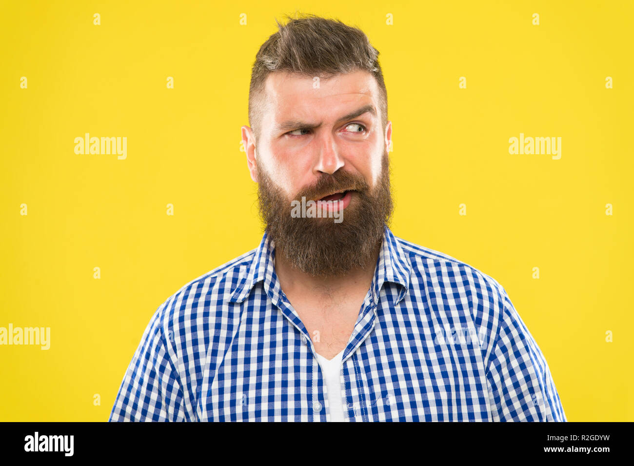 Sounds tricky. Man serious face raising eyebrow not confident. Have some doubts. Hipster bearded face not sure in something. Doubtful bearded man on yellow background close up. Doubtful expression. - Stock Image