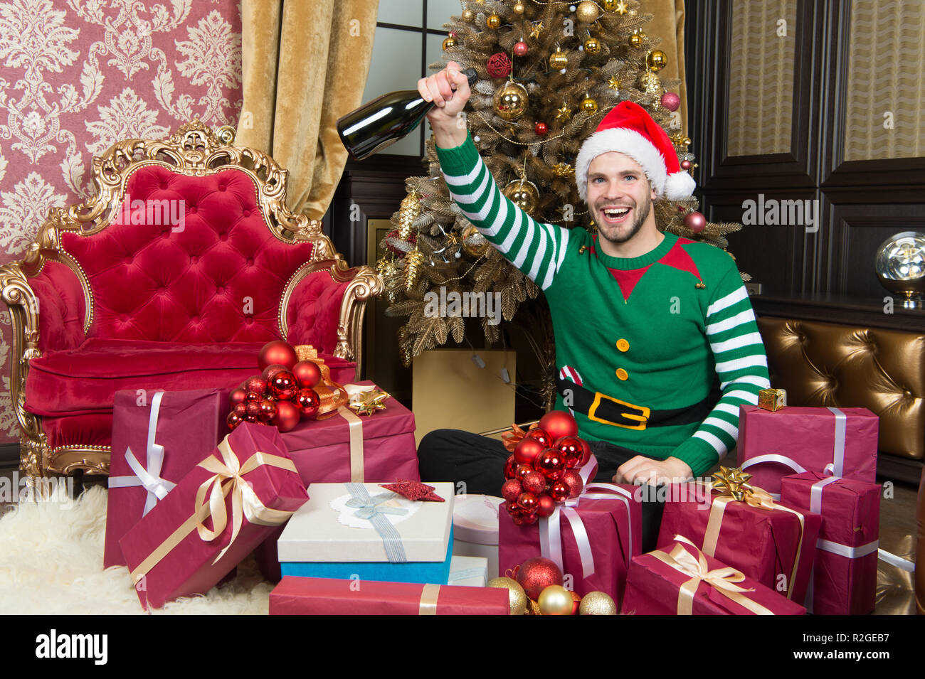 Happy holidays and a prosperous 2019. Man in santa hat hold new year presents. Guy is celebrating new year at home. Happy man with new year gift boxes. Merry Christmas and Happy New Year. - Stock Image