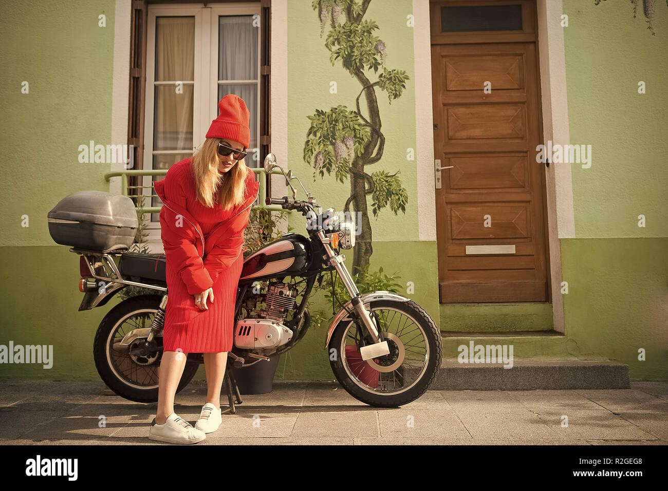 girl in fashionable red dress, hat and glasses, france. Woman biker at bike transport. Look and retro style. parisian fashion model near house and motorcycle. Beauty and vintage fashion. - Stock Image