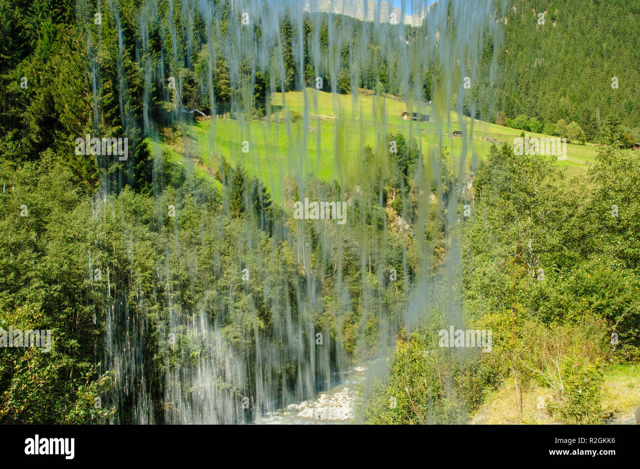 Tyrolean Alpine landscape as seen through a curtain of water from behind a waterfall. Photographed in Stubai Valley, Tyrol, Austria Stock Photo